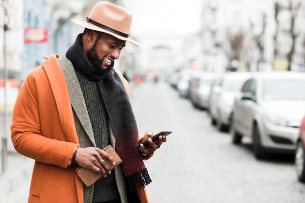 Hübscher mann in der orange jacke, die draußen mit kopienraum aufwirft