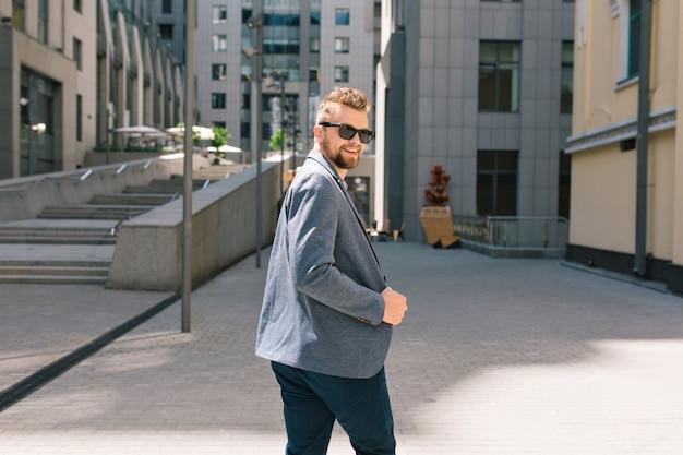 Hübscher mann in der sonnenbrille, die auf straße geht