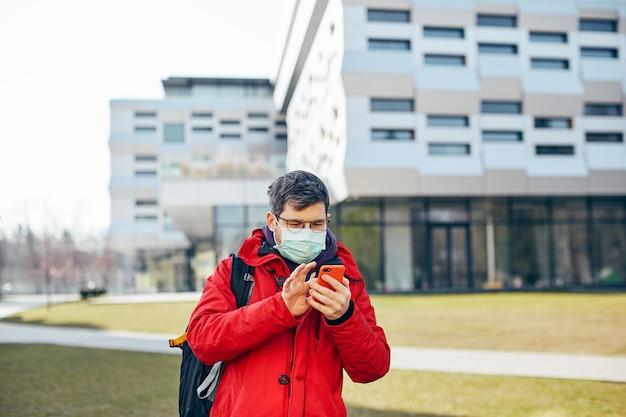 Hübscher mann in der sterilen schutzmaske, die auf der straße mit seinem telefon, kerl mit smartphone in der roten jacke in der modernen stadt steht
