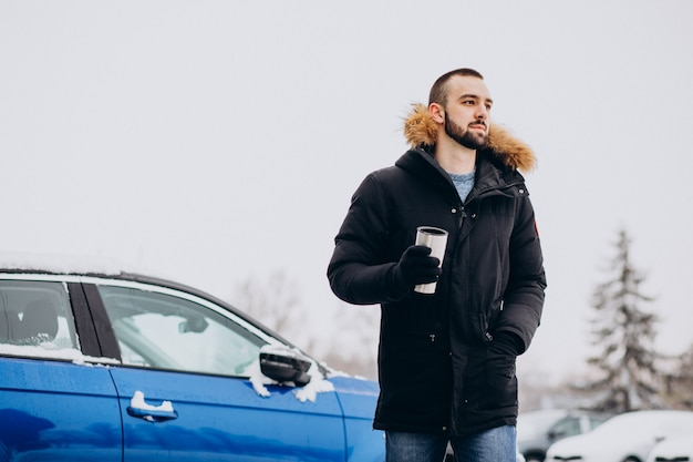 Hübscher mann in der warmen jacke, die durch auto steht, das mit schnee bedeckt ist und kaffee trinkt