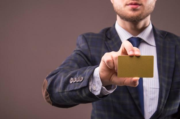 Hübscher mann in einem anzug, der eine visitenkartengoldfarbe hält