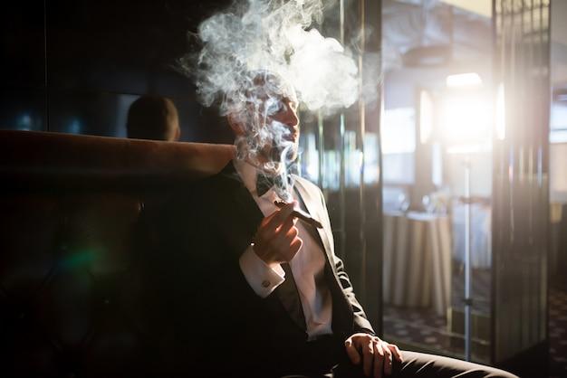 Hübscher mann in einem frack raucht eine zigarre