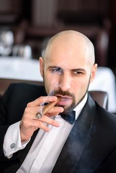 Hübscher mann in einem frack raucht