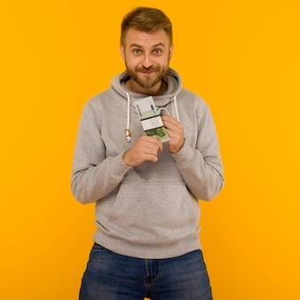 Hübscher mann in einem grauen kapuzenpulli genießt das gewinnen des lotteriegeld-euro auf einem gelben hintergrundbild