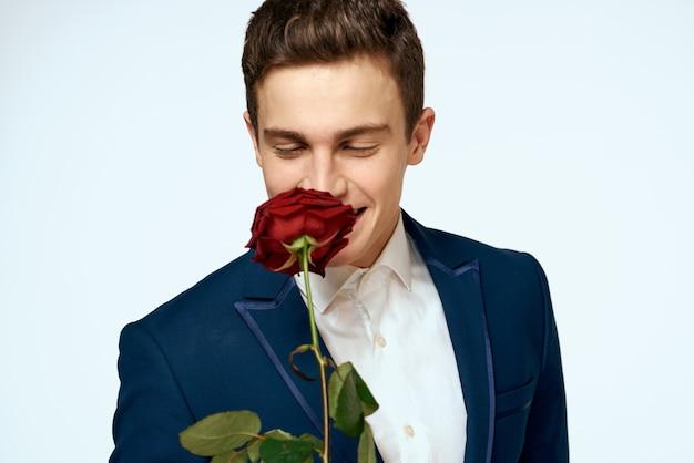 Hübscher mann in einem klassischen anzug mit einer rose in seinen händen