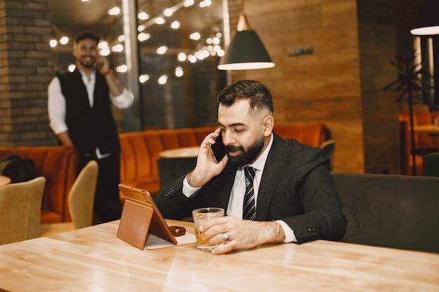 Hübscher mann in einem schwarzen anzug, der in einem café arbeitet