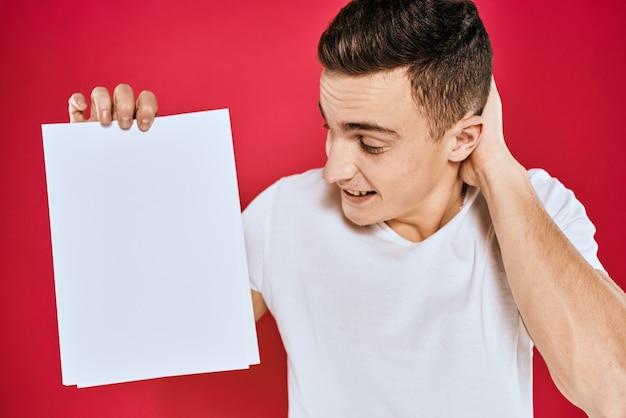 Hübscher mann in einem t-shirt, das ein leeres papier hält