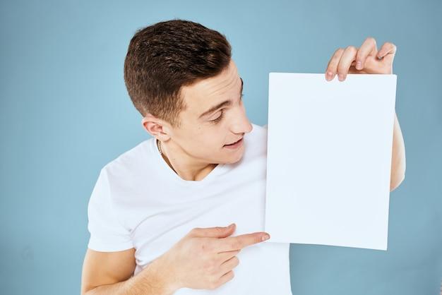 Hübscher mann in einem t-shirt hält ein weißes blatt ohne inschrift, freien platz, leeren raum, kopierraum
