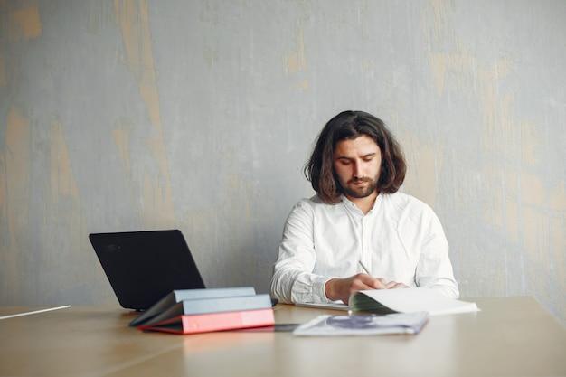 Hübscher mann in einem weißen hemd. geschäftsmann, der im büro arbeitet. kerl mit einem laptop.