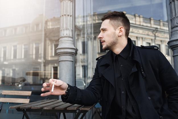 Hübscher mann in totalem schwarz, der zigarette hat und wegschaut.