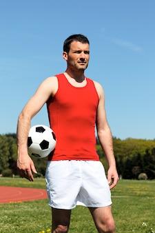 Hübscher mann mit ball unter dem arm