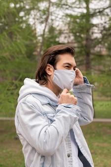 Hübscher mann mit braunen haaren, die im park gehen und stoffmaske auf gesicht während coronavirus-epidemie einstellen