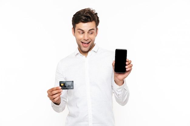 Hübscher mann mit dunklem haar, das smartphone und kreditkarte hält