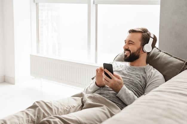 Hübscher mann mit europäischem aussehen in der grundkleidung, die auf der couch im haus liegt und musik unter verwendung des schwarzen handys hört, das drahtlose kopfhörer trägt