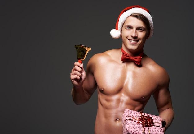 Hübscher mann mit glocke und weihnachtsgeschenk
