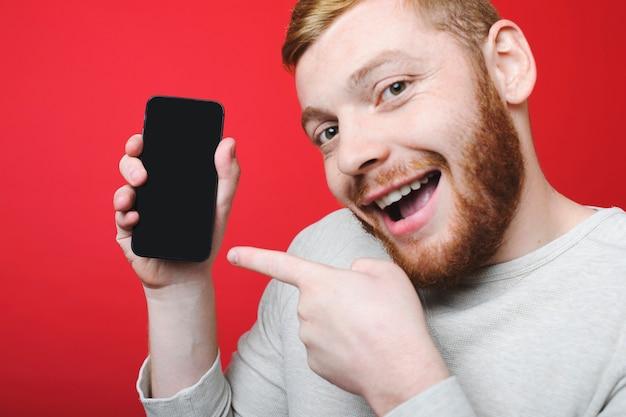 Hübscher mann mit ingwerbart, der auf smartphone mit leerem bildschirm zeigt und kamera betrachtet
