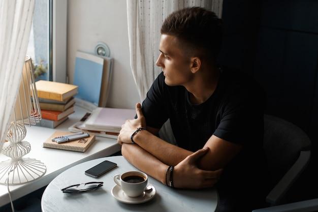 Hübscher mann mit kaffee, der im restaurant entspannt