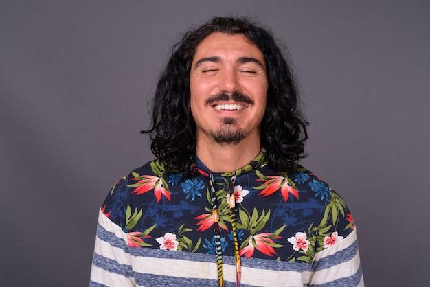 Hübscher mann mit lockigem haar und schnurrbart gegen grauen hintergrund