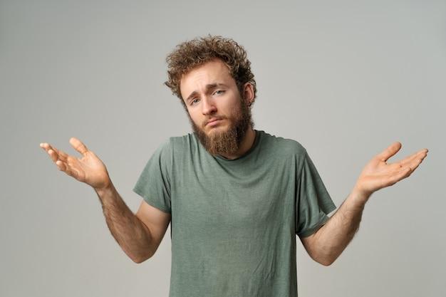 Hübscher mann mit lockigem haar zeigt, dass ich keine geste mit beiden händen isoliert kenne