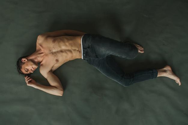 Hübscher mann mit nacktem oberkörper und haariger brust, die auf dem grünen boden in den jeans liegt.
