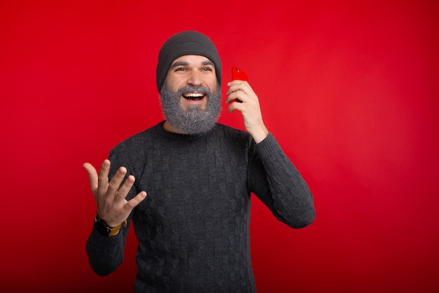 Hübscher mann mit weißem bart, der auf smartphone nahe rotem raum spricht