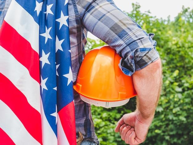 Hübscher mann mit werkzeugen, eine amerikanische flagge haltend. blick von hinten, nahaufnahme. konzept von arbeit und beschäftigung