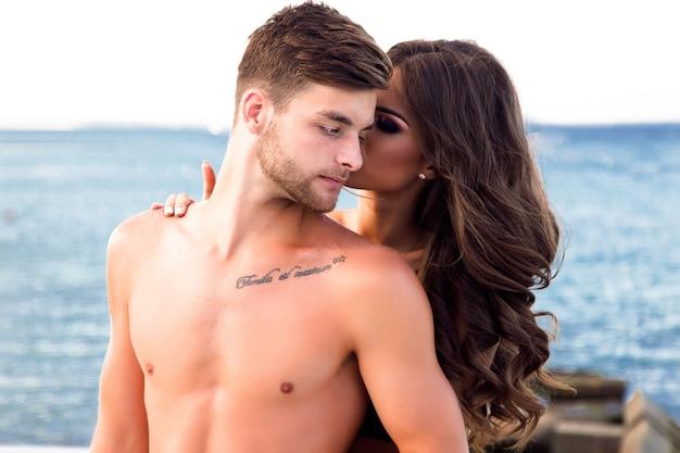 Hübscher mann mit wohlgeformtem körper, hat muskeln und bart, dame steht hinter ihm und küsst eine wange.