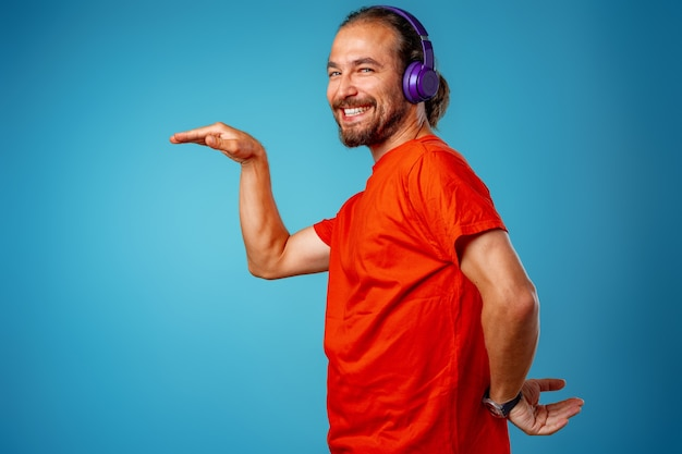 Hübscher mann mittleren alters, der musik mit blauen kopfhörern hört