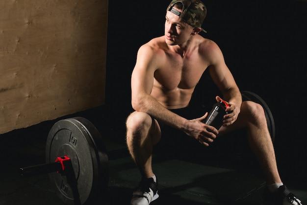 Hübscher mann müde nach gewichtheben im fitnessstudio