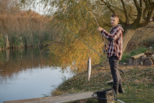 Hübscher mann nahe fluss an einem fischermorgen