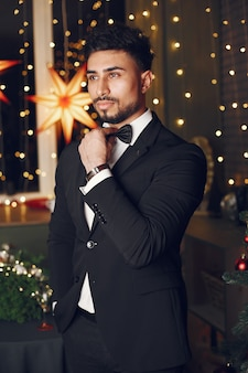 Hübscher mann nahe weihnachtsbaum. gentelman in einem schwarzen anzug.