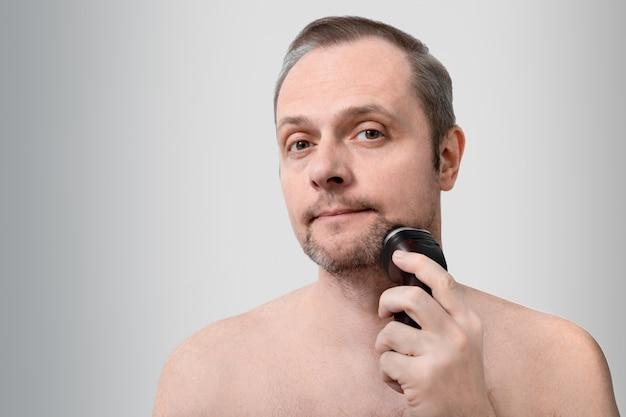 Hübscher mann rasiert sich mit einem elektrorasierer