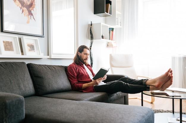 Hübscher mann sitzt und liest buch auf sofa zu hause