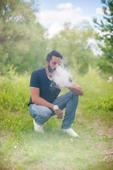 Hübscher mann sprengt ein paar eine elektronische zigarette an der frischen luft. der mensch mag den prozess des rauchens sehr.