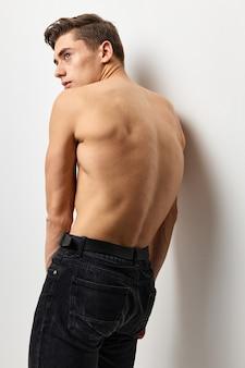 Hübscher mann steht mit seinem rücken nackt torso schwarze hose posiert.