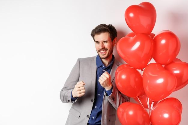 Hübscher mann tanzt und lächelt in der nähe von valentinstagherzenballon, zwinkert an der kamera, zieht sich am romantischen datum auf liebhaberfeiertag, weißer hintergrund an.