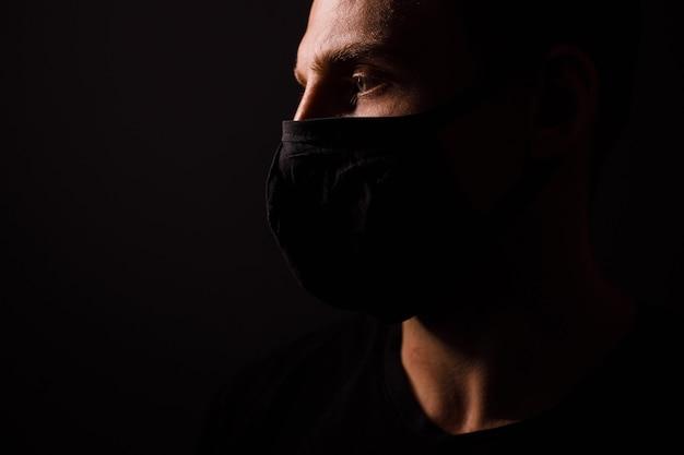 Hübscher mann tragen schwarze medizinische maske gegen coronavirus auf grauem hintergrund