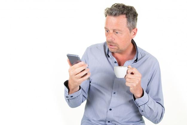 Hübscher mann über isolierte weiße sms-konversation auf handy mit heißem getränk tasse kaffee