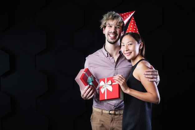 Hübscher mann und attraktive frau, die box mit geschenken auf einem schwarzen hintergrund betrachten. urlaubskonzept.