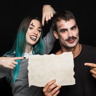 Hübscher mann und frau, die auf papierblatt zeigen