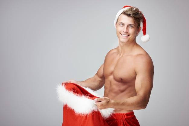 Hübscher mann und sack mit weihnachtsgeschenken
