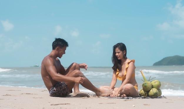 Hübscher mann und schöne frau im badeanzug, am strand sitzend, mit romantischem gefühl, modell posierend