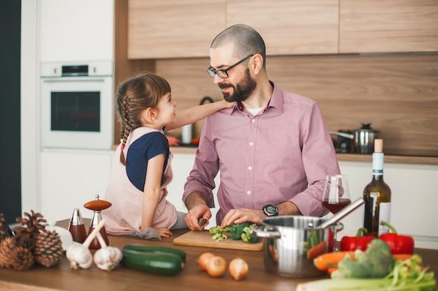 Hübscher mann und seine süße kleine tochter kochen zusammen gemüseeintopf in der küche. gesundes und vegetarisches lebensmittelkonzept.