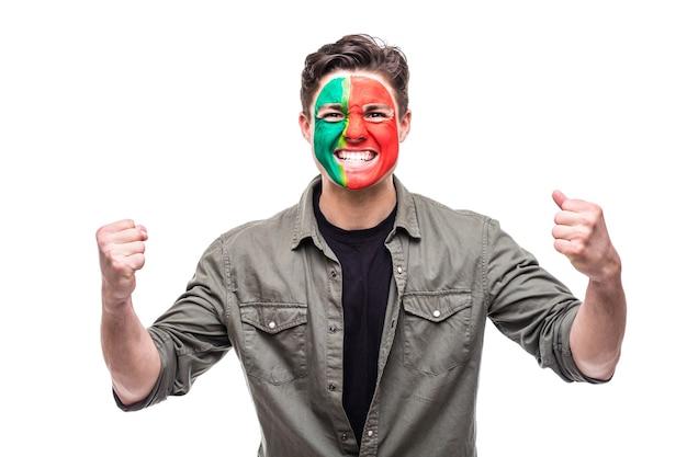 Hübscher mann unterstützer fan der portugiesischen nationalmannschaft gemaltes flaggengesicht erhalten glücklichen sieg, der in eine kamera schreit. fans emotionen.