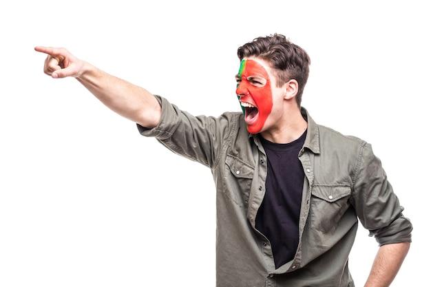 Hübscher mann unterstützer fan der portugiesischen nationalmannschaft gemaltes flaggengesicht erhalten glücklichen sieg schreiende spitze hand. fans emotionen.
