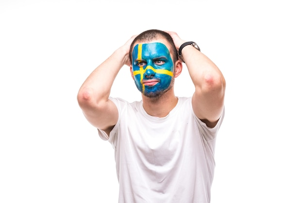 Hübscher mann unterstützer fan der schwedischen nationalmannschaft gemalt flagge gesicht bekommen unglückliche traurige frustrierte emoitions in eine kamera. fans emotionen.