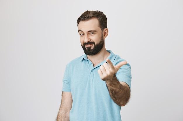 Hübscher mann zeigt mit dem finger, sagen sie, kommen sie näher