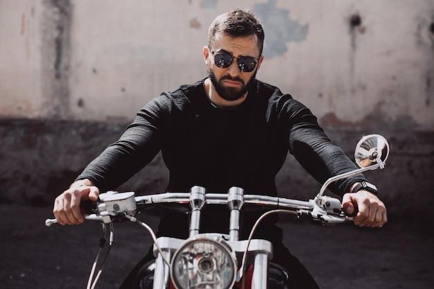 Hübscher mannbiker, der auf motorrad fährt