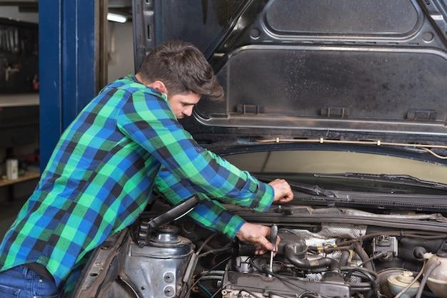 Hübscher mechaniker, der am telefon bei der reparatur eines autos spricht.