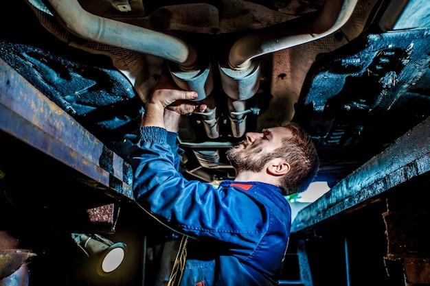 Hübscher mechaniker in der uniform arbeiten im selbstservice mit angehobenem fahrzeug.